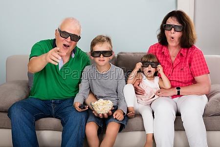 grandparent and grandchildren watching 3d movie