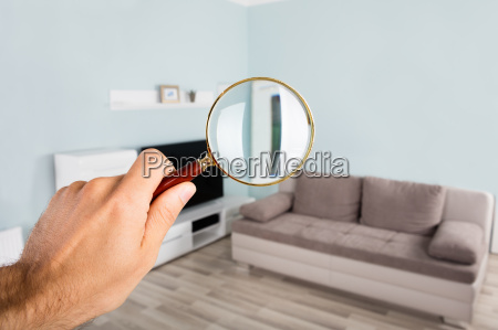 person checking living room using magnifying