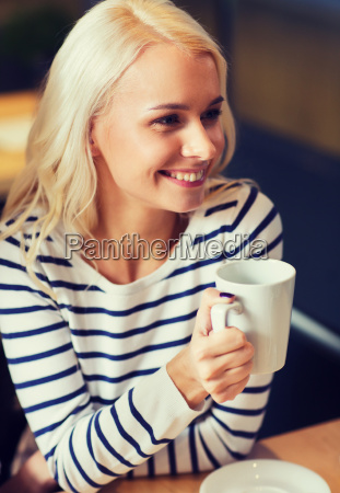 happy young woman drinking tea or