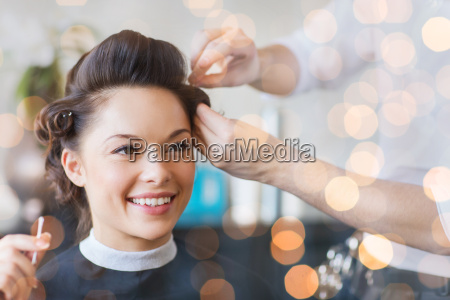 happy woman with stylist making hairdo