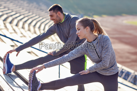couple stretching leg on stands of