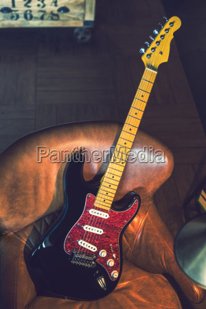 electric guitar leaning against a couch