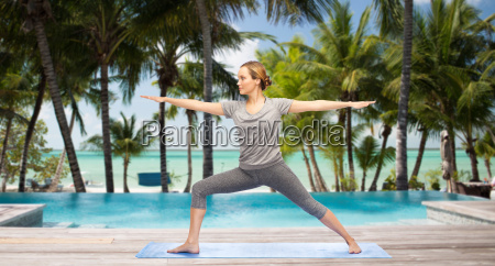 woman making yoga warrior pose over