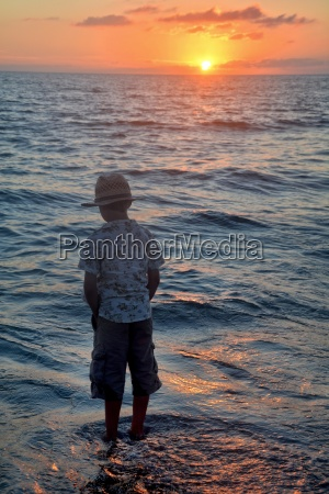 little boy stands in the waves