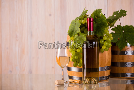 bottle of wine with barrels grapes