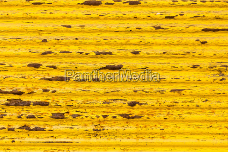 rusty yellow paint on old fence