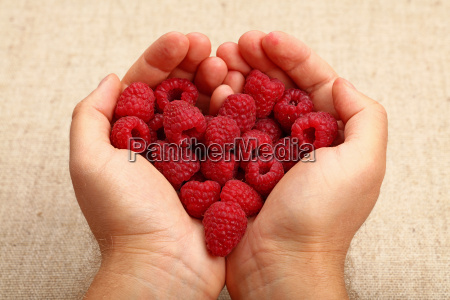 man hands with heart shaped raspberries