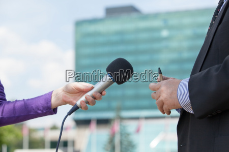 female journalist interviewing businessman corporate building