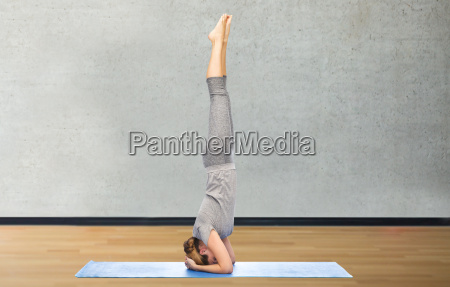 woman making yoga in headstand pose