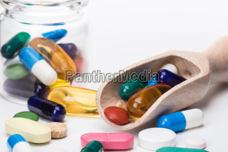 color pills in glass container and
