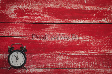 old black clock on wooden red