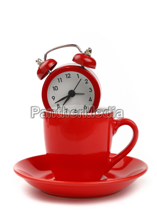 red alarm clock in coffee cup