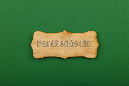 figured shaped wooden sign on green