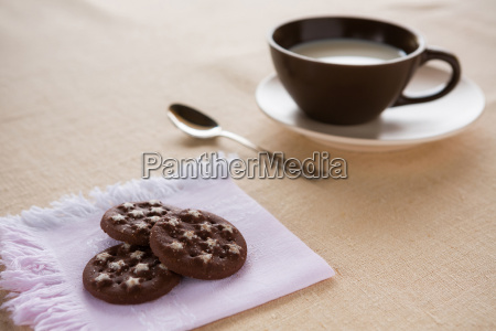 a cup of milk with biscuits