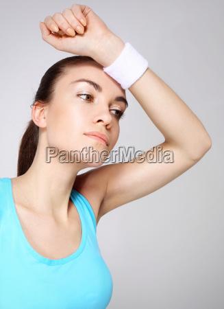 beautiful sportswoman wipes sweat from her