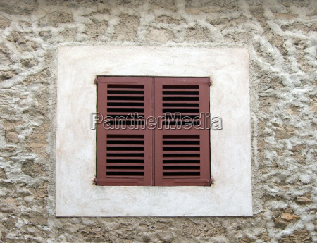 window with closed wooden shutters in