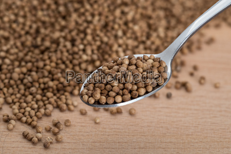 organic coriander seeds on wooden cutting