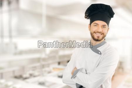 glad smilende kok staende i kokkenet