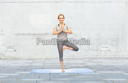 woman making yoga in tree pose