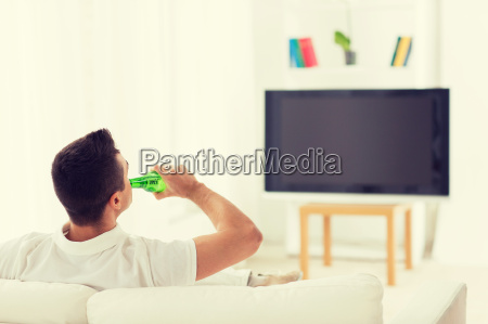 man watching tv and drinking beer