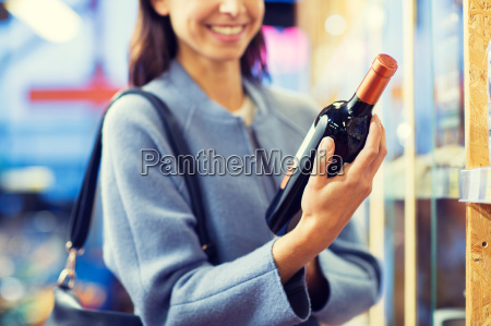 happy woman choosing and buying wine