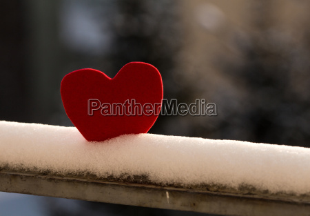 lonely heart on snowy railing