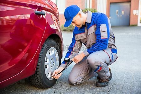 man measuring car tyre pressure