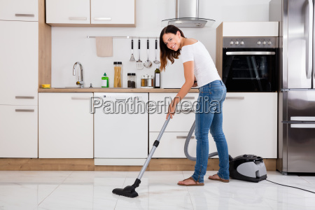 woman using vacuum cleaner to clean
