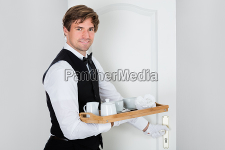 happy young waiter carrying coffee set