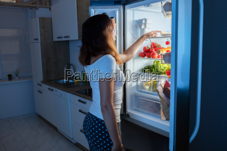woman looking at food in refrigerator