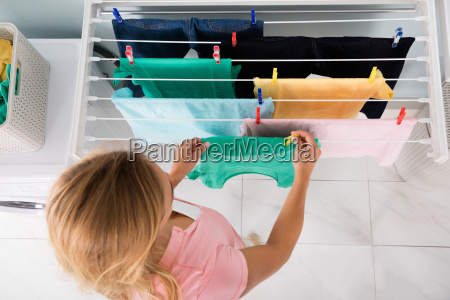 woman hanging wet cloth on clothes