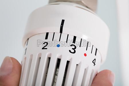 person adjusting thermostat radiator valve