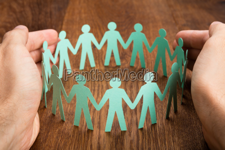 person protecting cut out figures on