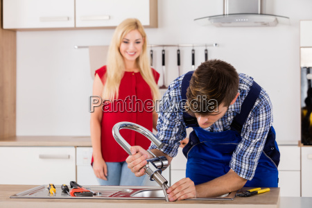 male repairman installing faucet of kitchen