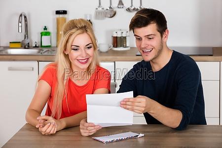 happy couple reading letter on desk
