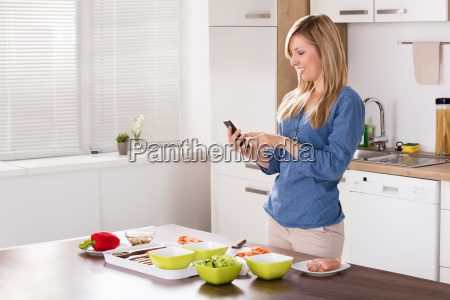 smiling woman using mobilephone in kitchen