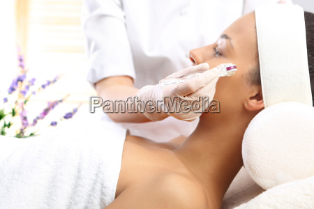 a beautician performs a needle mesotherapy