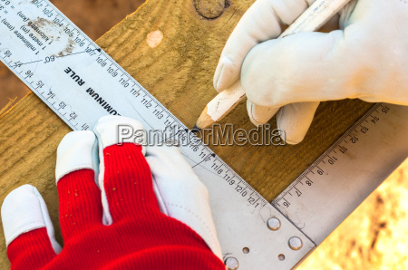 hand of a carpenter taking measurement