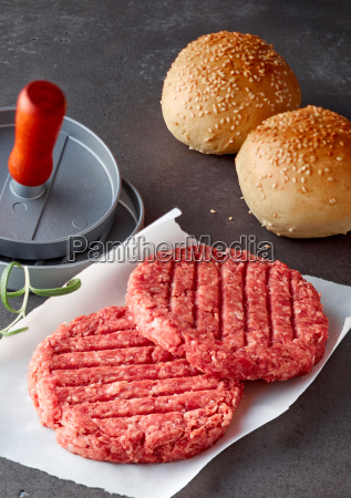 raw beef hamburger patties with press
