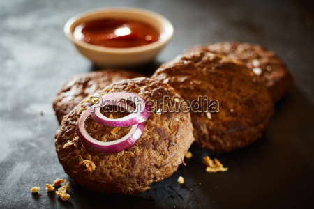 cooked burger patties with red onion