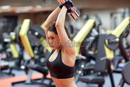 young woman flexing muscles with dumbbell