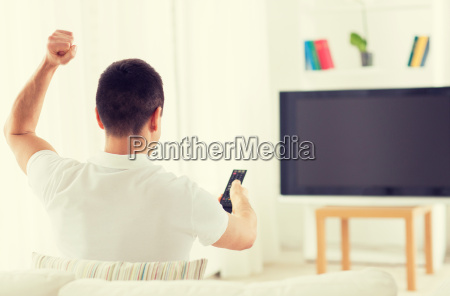 man watching tv and supporting team