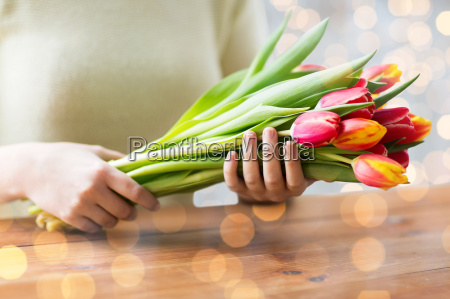 close up of woman holding tulip