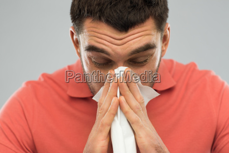 sick man blowing nose to paper