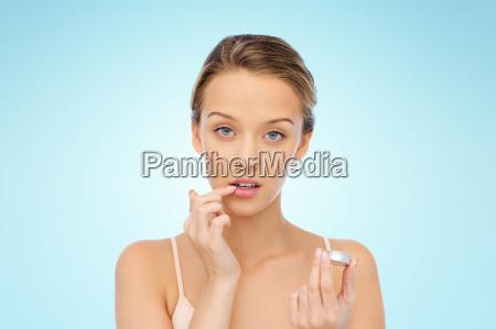 young woman applying lip balm to