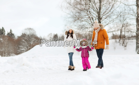 happy family in winter clothes walking