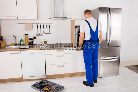 technician repairing oven in kitchen