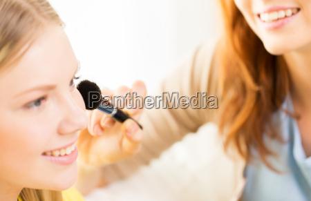 happy women with makeup brush applying