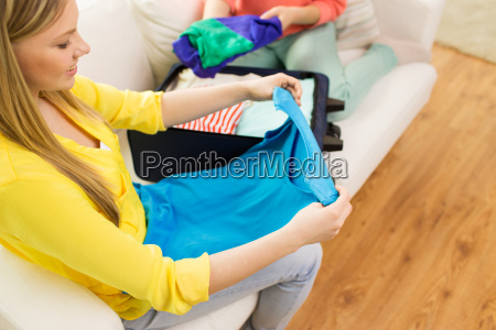 young woman packing clothes into travel