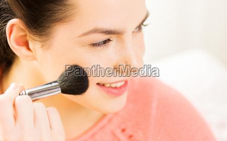 happy woman with makeup brush blushing